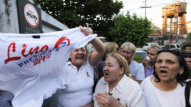 Supporters of the late Paraguayan presidential candidate Lino Cesar Oviedo demonstrate outside the morgue where his remains were taken after he died in a helicopter crash in Asuncion, Paraguay, Sunday, Feb. 3, 2013. Oviedo was returning with his bodyguard from a political rally in northern Paraguay Saturday night when his pilot encountered bad weather. All three were killed in the crash, said Johnny Villalba, a spokesman for Paraguay's airport authority. (AP Photo/Jorge Saenz)