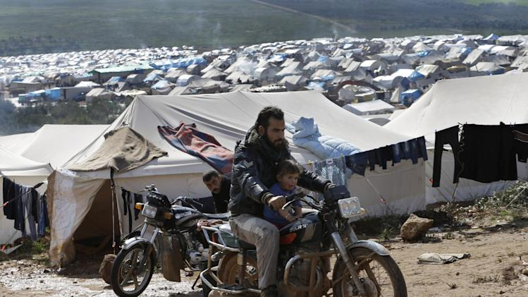 In this Tuesday, Feb. 19, 2013 photo, a Syrian refugee rides his motorcycle with his son at Atmeh refugee camp, in the northern Syrian province of Idlib, Syria. This rebel-controlled camp only yards from the border with Turkey houses some 16,000 people displaced by the civil war. But the U.N. and other major aid agencies best equipped to handle such a large-scale relief agency cannot reach them because they are inside Syria. That leaves the job to smaller organizations who can only provide a fraction of the needs.(AP Photo/Hussein Malla)