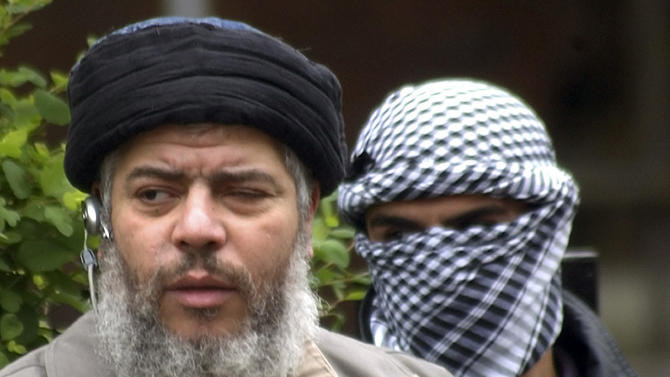 FILE - In this April 30, 2004 file photo, Muslim cleric Mustafa Kamel Mustafa arrives with a masked bodyguard to conduct Friday prayers in the street outside the closed Finsbury Park Mosque in London. The 55-year-old Egyptian cleric, who also goes by the alias Abu Hamza al-Masri, was found guilty on Monday, May 19, 2014 in federal court in New York of providing material support to terrorist organizations. (AP Photo/Max Nash, File)