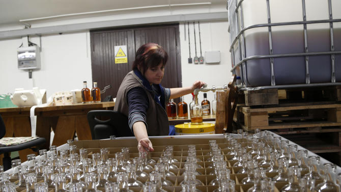 """To go with story """"Czech Communist Whisky"""" by Karel Janicek - In this Monday, April 8, 2013 photo Eva Brozovska fills bottles with single malt """"Hammer Head"""" whisky in a distillery in Pradlo, Czech Republic. The """"Hammer Head"""" whisky made in communist Czechoslovakia matured in oak barrels for more than twenty years to reach surprisingly good quality before hitting the market. (AP Photo/Petr David Josek)"""