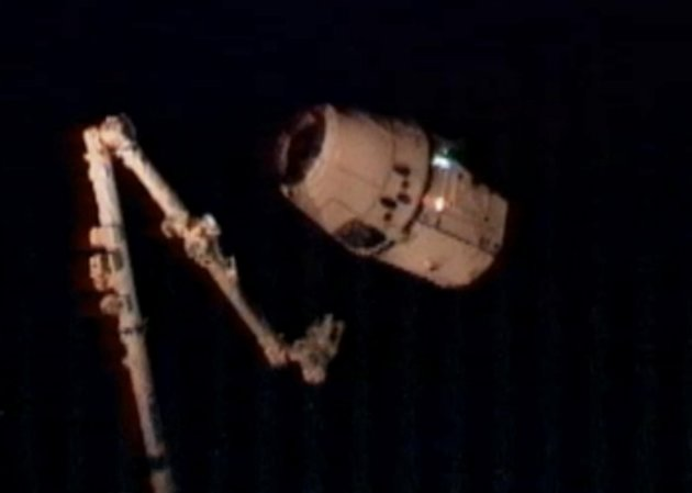 This image provided by NASA-TV shows the SpaceX Dragon commercial cargo craft, top, as Dragon approaches the International Space Station, and Expedition 31 Flight Engineers Don Pettit and Andre Kuiper