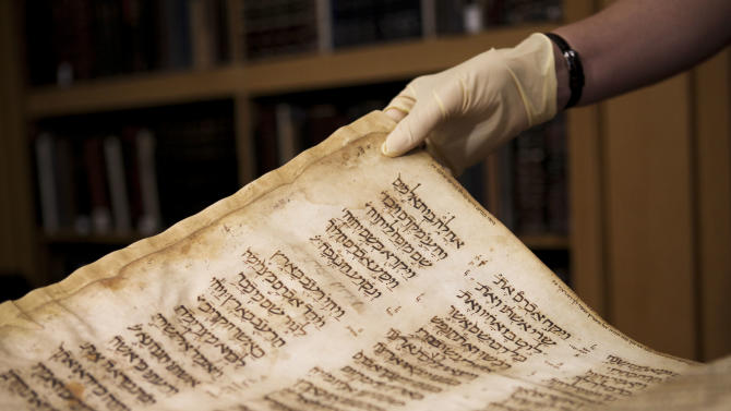 An Israeli librarian turns the page in a rare book before it is exhibited at the National Library in Jerusalem, Wednesday, Oct. 5, 2011. Precious Bible manuscripts originating in the Jewish community of Damascus, Syria, went on display for several hours Wednesday, offering a rare glimpse at a collection that includes books spirited to Israel in clandestine operations before the ancient community disappeared at the end of the 20th century. (AP Photo/Tara Todras-Whitehill)