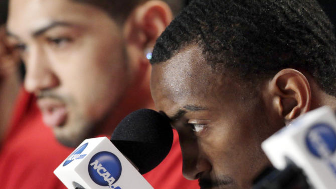 Louisville guard Russ Smith stares at a microphone during a news conference, Saturday, March 30, 2013, in Indianapolis. Louisville is scheduled to play Duke in the Midwest Regional final in the NCAA college basketball tournament on Sunday. At left is guard Peyton Siva. (AP Photo/Kiichiro Sato)