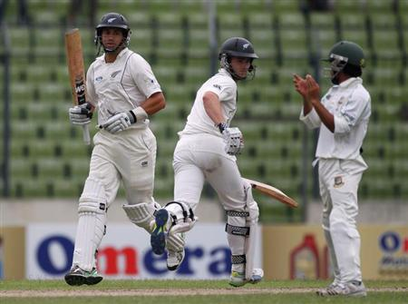 New Zealand's Ross Taylor (L) and Kane Williamson run between the wickets as Bangladesh's Mominul Haque (R) watches, during their second day of second test cricket match of the series in Dhaka October