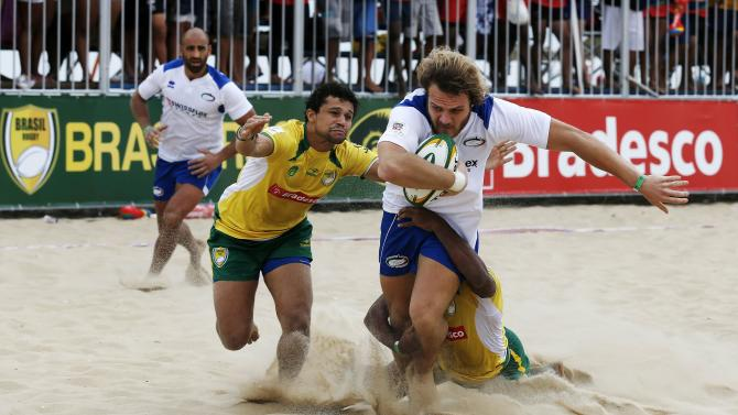 Susio of Italy is tackled by Estrela and Veiga of Brazil as Nitoglia of Italy looks on during their men's Beach Rugby International tournament match at Ipanema beach in Rio de Janeiro