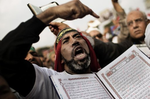 "<p>A supporter of Egypt's President Mohamed Morsi and the Muslim Brotherhood holds a copy of the Koran in Cairo's Nasr City on December 14, 2012. The opposition accused President Mohamed Morsi's Muslim Brotherhood of attempted ""vote rigging"" in Saturday's referendum on a new constitution for Egypt.</p>"