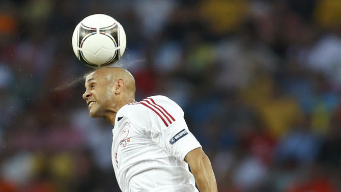 Denmark's Simon Busk Poulsen heads the ball as Arjen Robben from the Netherlands watches during the Euro 2012 soccer championship Group B match between the Netherlands and Denmark in Kharkiv , Ukraine, Saturday, June 9, 2012. (AP Photo/Vadim Ghirda)