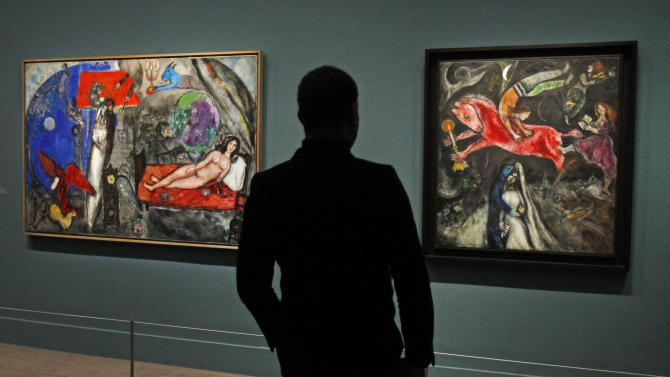 A member of the media views a painting by Russian artist Marc Chagall before the opening of the exhibition: Chagall, between War and Peace, at the Luxembourg museum in Paris, Tuesday Feb. 19, 2013. The exhibition starts February 21 and ends July 21, 2013.  Painting at right is: 1944, Le  Cheval Rouge, and at left: 1944, A Ma Femme.(AP Photo/Remy de la Mauviniere)