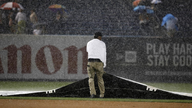 A member of the grounds crew pulls the tarp on the field after a heavy rainstorm interrupted the fifth inning of a baseball game between the Texas Rangers and the New York Yankees at Yankee Stadium in New York, Wednesday, July 23, 2014. (AP Photo)