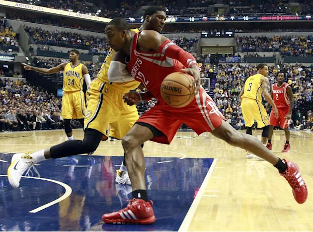 Houston Rockets center Dwight Howard (12) pushes into Indiana Pacers center Roy Hibbert while driving to the basket in the first half of an NBA basketball game in Indianapolis, Friday, Dec. 20, 2013
