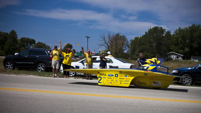 In this Saturday, July 21, 2012 photo provided by the University of Michigan, supporters of the University of Michigan's entry in the 2012 American Solar Challenge cheer as the solar vehicle, the Quantum, comes in to win the eight-day event in St. Paul, Minn. University of Michigan teams have won the  competition four times in a row and seven times since the event started in 1990. The race started July 14, 2012 in Rochester, N.Y. Iowa State finished second and Principia College was third this year. (AP Photo/University of Michigan, Diane Thach)