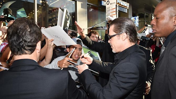 "Brad Pitt signs autographs at the world premiere of ""Maleficent"" at the El Capitan Theatre on Wednesday, May 28, 2014, in Los Angeles. (Photo by John Shearer/Invision/AP)"