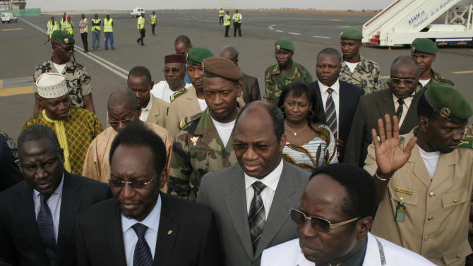 Dioncounda Traore, front second left, Mali's parliamentary head who was forced into exile after last month's coup, walks with Burkina Faso Foreign Affairs Minister Djibrill Bassole, center in gray, as Traore arrives at the airport to take up his constitutionally-mandated post as interim president, in Bamako, Mali Saturday, April 7, 2012. Traore's return comes after coup leader Capt. Amadou Haya Sanogo signed an accord late Friday, agreeing to return the nation to constitutional rule.(AP Photo/Harouna Traore)