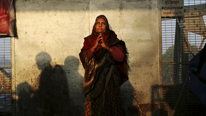 An Indian woman stands on a platform near where a stampede took place a night before, at the station in Allahabad, India, Monday, Feb. 11, 2013. The death toll from the stampede rose to 36 on Monday in the northern India city where millions of devotees had gathered for a Hindu festival that is one of the world's largest religious gatherings. (AP Photo/Kevin Frayer)