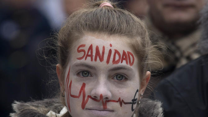 A demonstrator takes part in a National health workers march during the first major demonstration of the year, in Madrid,  Monday Jan. 7, 2013. The demonstration was against government-imposed austerity measures and labor reforms in the public health care sector in Madrid. Word painted on her face reads' Health.' (AP Photo/Paul White)