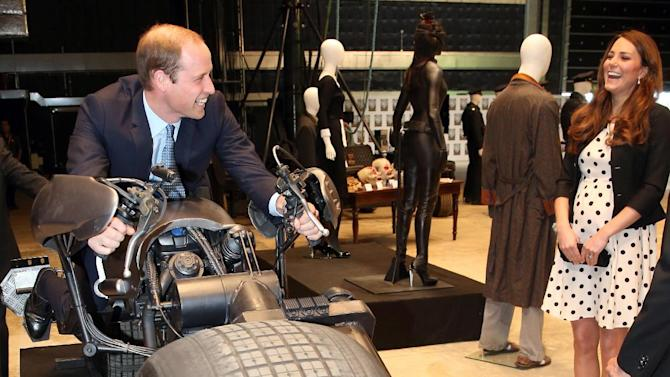 """Britain's Kate the Duchess of Cambridge watches her husband Prince William as he sits on the 'Batpod' during the inauguration of """"Warner Bros. Studios Leavesden"""" near Watford, approximately 18 miles north west of central London, Friday, April 26, 2013. As well as attending the inauguration Friday at the former World War II airfield site, the royals will undertake a tour of Warner Bros. """"Studio Tour London - The Making of Harry Potter"""", where they will view props, costumes and models from the Harry Potter film series. (AP Photo/Chris Jackson, Pool)"""