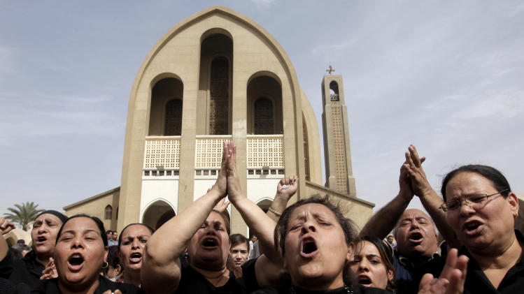 Egyptian Christians chant anti-Muslim Brotherhood slogans following a funeral service at the Saint Mark Coptic cathedral in Cairo, Egypt, Sunday, April 7, 2013. Several Egyptians including 4 Christians and a Muslim were killed in sectarian clashes before dawn in Qalubiya, just outside of Cairo on Saturday, April 6, 2013. (AP Photo/Amr Nabil)