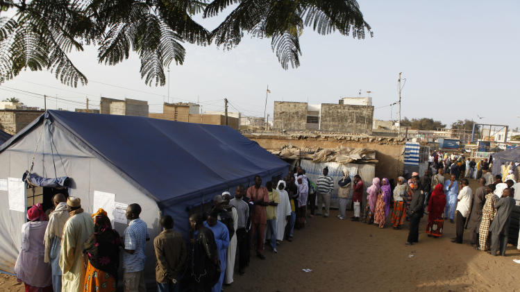 Voters wait in line to cast their votes outside tents erected to serve as polling stations, in the Guediawaye neighborhood of Dakar, Senegal Sunday, March 25, 2012. Senegalese president Abdoulaye Wade, whose decision to run for a controversial third term sparked violent pre-election protests, faces his former protege Macky Sall in Sunday's presidential run-off.(AP Photo/Rebecca Blackwell)