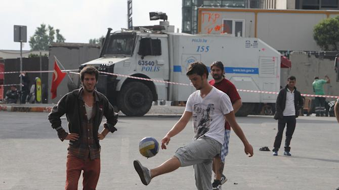 Protesters play soccer as a police water cannon is parked in the background at the Taksim Square in Istanbul on Thursday, June 13, 2013. Turkey's government on Wednesday offered a first concrete gesture aimed at ending nearly two weeks of street protests, proposing a referendum on a development project in Istanbul that triggered demonstrations that have become the biggest challenge to Prime Minister Recep Tayyip Erdogan's 10-year tenure. (AP Photo/Thanassis Stavrakis)