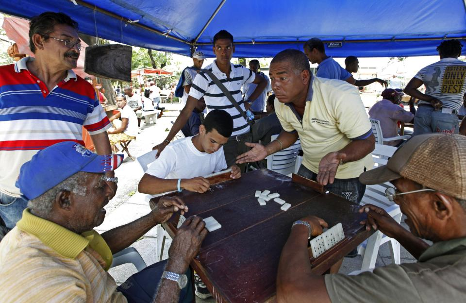 This April 24, 2012 photo shows a group of men playing a game of dominoes at a park in Santiago de Cuba, Cuba.  (AP Photo/Kathy Willens)