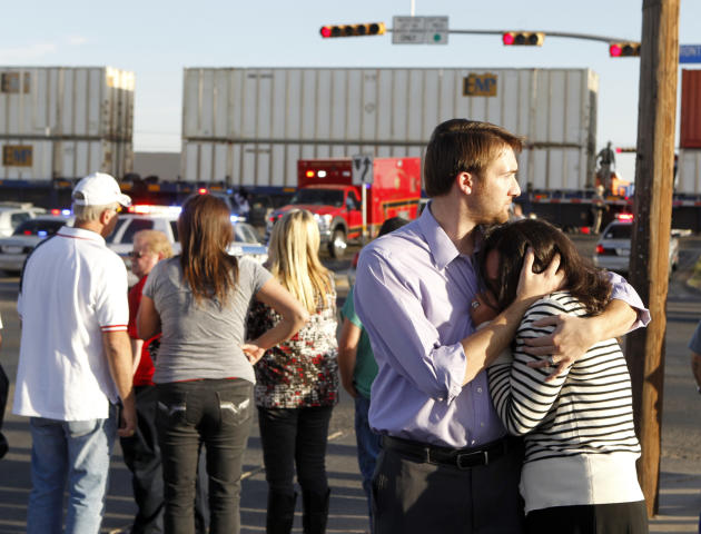 "Bystanders react as emergency personnel work the scene where a trailer carrying wounded veterans in a parade was struck by a train in Midland, Texas, Thursday, Nov. 15, 2012. ""Show of Support"" preside"