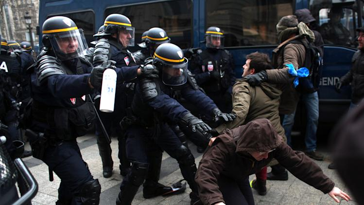 """Protestors clash with riot police officers during an anti gay marriage and gay adoption demonstration, in Paris, Sunday, March. 24, 2013. Thousands of French conservatives, families and activists have converged on the capital to try to stop the country from allowing same-sex couples to marry and adopt children. The lower house of France's parliament approved the """"marriage for everyone"""" bill last month with a large majority, and it's facing a vote in the Senate next month. Both houses are dominated by French President Francois Hollande's Socialist Party and its allies. (AP Photo/Thibault Camus)"""