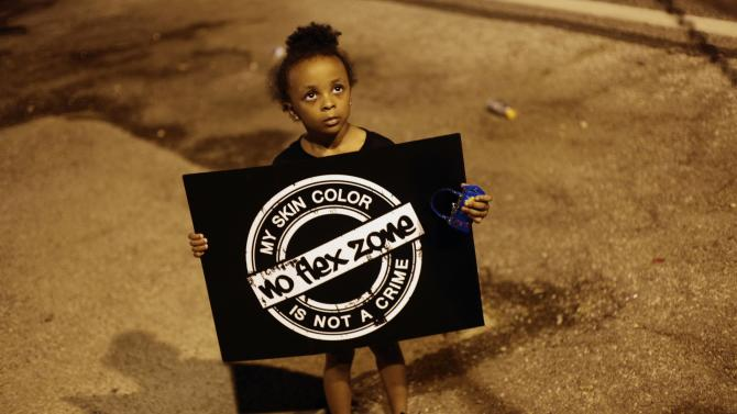 A girl holds a sign as she protests the shooting of Michael Brown August 21, 2014 in Ferguson, Missouri