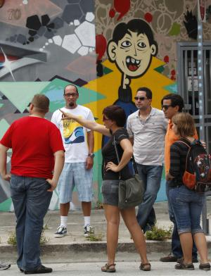 In this Thursday, June 30, 2011 photo, Kit Sullivan, center, of Roam Rides, speaks during a two-hour graffiti tour in the Wynwood neighborhood of Miami. Once derided as vandalism, graffiti in the form of artistic murals has become an accepted art form in Miami's Wynwood neighborhood. Now visitors can take a two-hour tour by Vespa of the area's best graffiti.  (AP Photo/Wilfredo Lee)