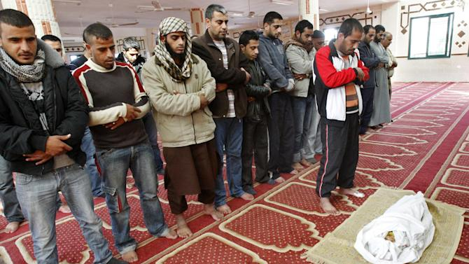 Palestinians pray over the body of one and a half year-old baby, Iyad Abu Khoussa, during his funeral at a mosque in Bureij Refugee Camp, central Gaza Strip, Sunday, Nov. 18, 2012. The baby boy was one of five Palestinian children killed in Israeli strikes on Sunday, according to a Gaza health official. (AP Photo/Adel Hana)