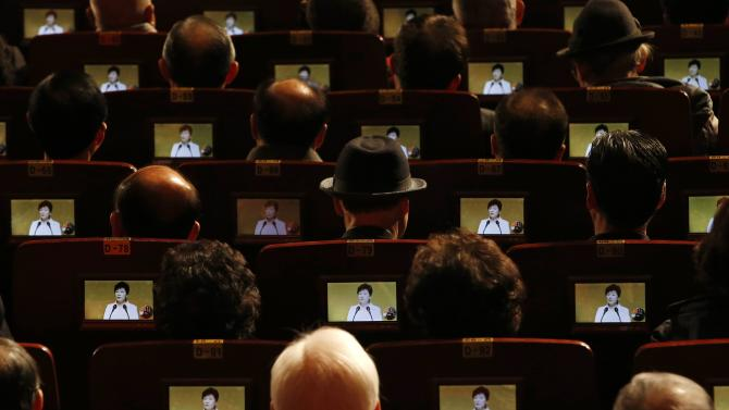 People watch South Korean President Park Geun-hye's speech on small screens during a ceremony celebrating the 96th anniversary of the Independence Movement Day in Seoul