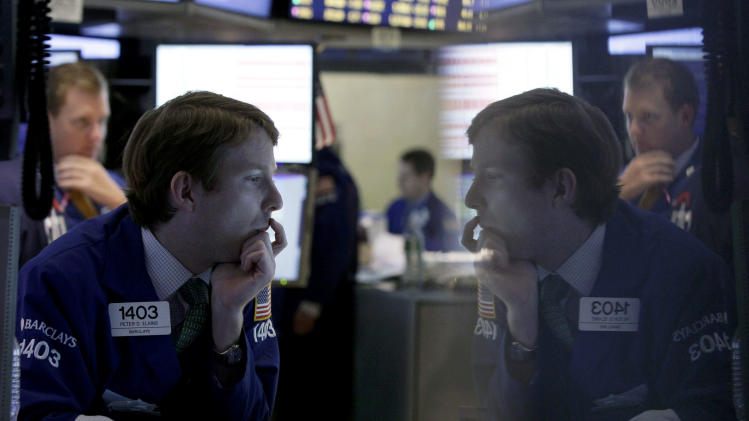 """FILE - In this Tuesday, Oct. 23, 2012 file photo, specialist Peter Elkins, foreground, is reflected in a trading post monitor as he works on the floor of the New York Stock Exchange, in New York. If Washington lawmakers can get past the """"fiscal cliff,"""" many analysts say that the outlook for stocks in 2013 is good, as a recovering housing market and an improving jobs outlook helps the economy maintain a slow, but steady recovery. (AP Photo/Richard Drew, File)"""