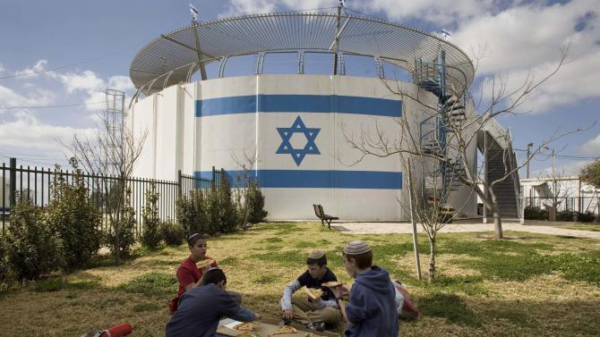 Israeli children eat pizza next to a water tank near the West Bank Jewish settlement of Beit El, near the West Bank city of Ramallah, Tuesday, March 1, 2011. Israeli Prime Minister Benjamin Netanyahu is a longtime settlement advocate. But on Monday, he hinted that Israel might have to curb its settlement ambitions in response to pressure from the international community, which deplores the construction on lands the Palestinians want for a future state. (AP Photos / Bernat Armangue)