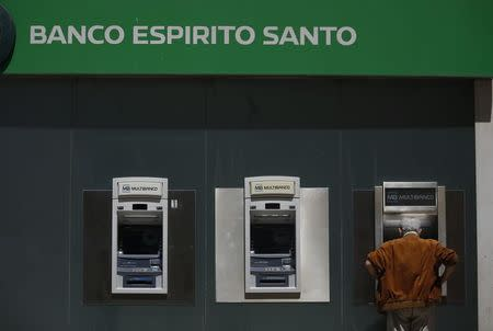 A man uses an automated teller machine of Portuguese bank Banco Espirito Santo in downtown Lisbon
