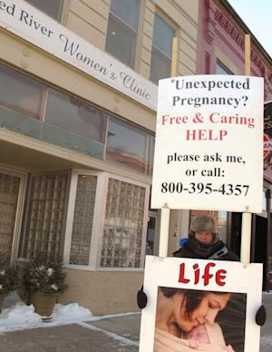 """FILE - This Feb. 20, 2013 file photo shows a protesters outside the Red River Valley Women's Clinic, the state's sole abortion provider, in Fargo, N.D. A federal judge overturned a North Dakota law Wednesday, April 16, 2014 that bans abortions when a fetal heartbeat can be detected, as early as six weeks into pregnancy and before many women know they're pregnant. The Bismarck judge said the law is """"invalid and unconstitutional"""" and that it """"cannot withstand a constitutional challenge."""" (AP Photo/Dave Kolpack, File)"""