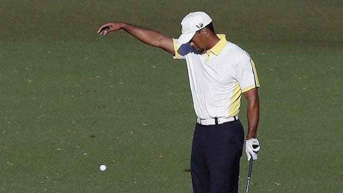 Tiger Woods takes a drop on the 15th hole after his ball went into the water during the second round of the Masters golf tournament Friday, April 12, 2013, in Augusta, Ga. The drop is being reviewed by the rules committee. (AP Photo/Charlie Riedel)