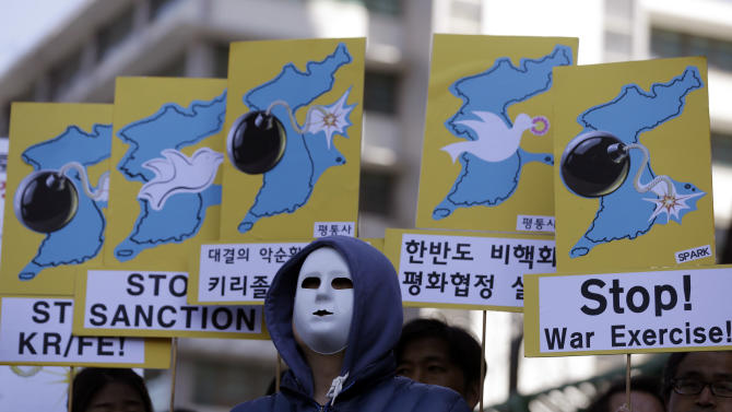 South Korean protesters wearing masks hold placards during a rally denouncing the annual joint military exercises, dubbed Key Resolve and Foal Eagle, between South Korea and the United States, near the U.S. Embassy in Seoul, South Korea, Monday, March 11, 2013. South Korea and the United States began annual military drills Monday despite North Korean threats to respond by voiding the armistice that ended the Korean War and launching a nuclear attack on the U.S. (AP Photo/Lee Jin-man)