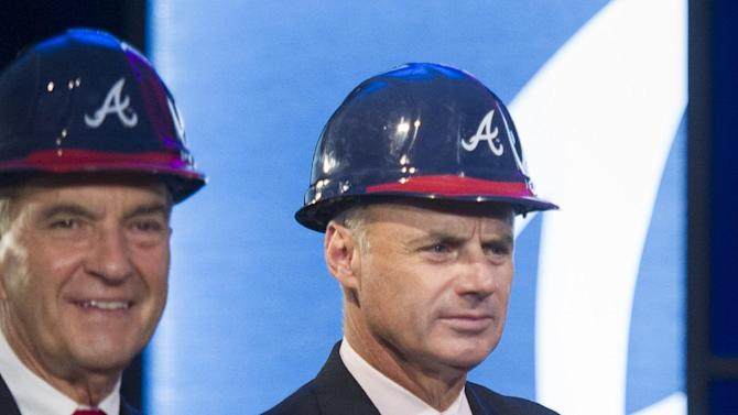 Baseball Commissioner-elect Rob Manfred, right, waits along with Atlanta Braves president John Schuerholz during a groundbreaking ceremony Tuesday, Sept. 16, 2014, in Atlanta, for the Atlanta Braves new baseball stadium, which will be called SuntTust Park. The Braves will be moving from Turner Field in Fulton County to the new stadium being built in Cobb County in 2017. (AP Photo/John Amis)