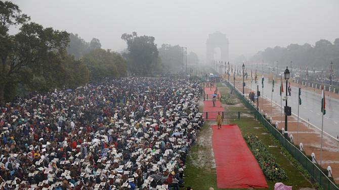 A crowd gathers to watch Republic Day parade as it rains in New Delhi, India, Monday, Jan. 26, 2015. Republic Day marks the anniversary of India's democratic constitution taking force in 1950. Beyond the show of military power, the parade includes ornate floats highlighting India's cultural diversity. (AP Photo /Manish Swarup)