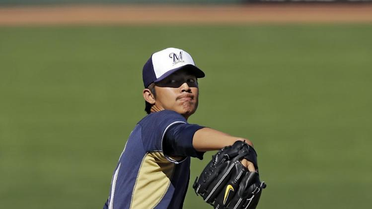 Milwaukee Brewers starting pitcher Wei-Chung Wang, from Taiwan, delivers against the Cleveland Indians in the fifth inning of a spring exhibition baseball game on Sunday, March 9, 2014, in Goodyear, Ariz