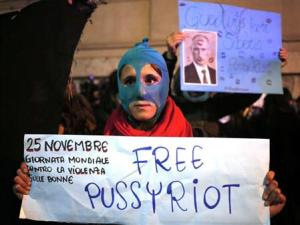 A demonstrator holds a placard supporting Pussy Riot in front of Quirinale palace in Rome, as Russia's President Vladimir Putin visits his Italian counterpart Giorgio Napolitano, November 25, 2013. Putin is on a two-day visit to Italy and Vatican. REUTERS/Yara Nardi/Files