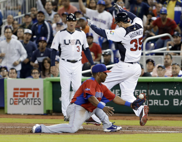 United States' Eric Hosmer (35) is safe at first base as Dominican Republic first baseman Edwin Encarnacion is unable to hold on to the ball during the sixth inning of a second-round game of the World