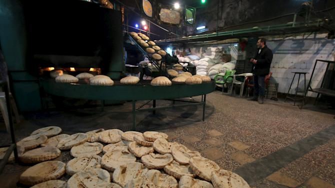 A man stands near bread cooling down after being baked inside a bakery in the rebel held al-Shaar neighborhood of Aleppo