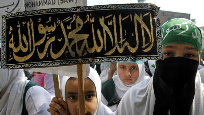 """Kashmiri Muslim students hold placards as they participate in a protest rally against an anti-Islam film called """"Innocence of Muslims"""" that ridicules Islam's Prophet Muhammad, in Srinagar, India, Saturday, Sept. 22, 2012. The placard reads: """"There is no God but Allah and Muhammad is his messenger."""" (AP Photo/Mukhtar Khan)"""
