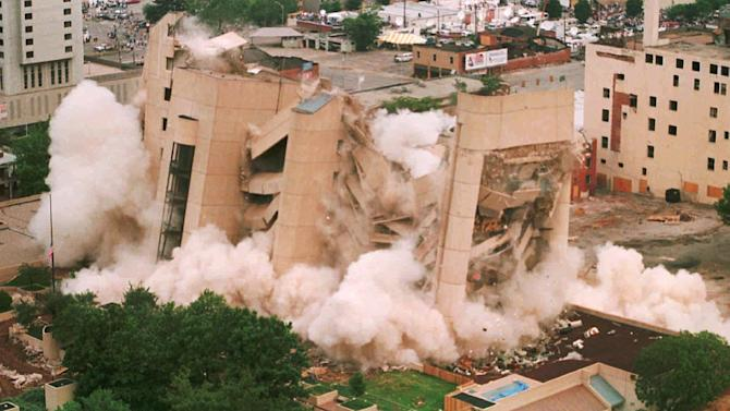 FILE - In this May 23, 1995 file photo, the Alfred P. Murrah Federal Building in downtown Oklahoma City falls in a cloud of dust as it was demolished by exposives. The building was the site of a deadly car-bomb attack April 19, 1995. A memorial to the bombing's victims now sits on the former site of the federal building, and a nearby building that was damaged in the bombing houses an interactive museum. (AP Photo/Jerry Laizure/POOL)