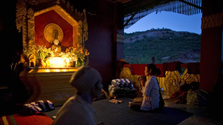 A devotee prays at a Buddhist shrine that is schedule to be dismantle for the expansion of the Letpadaung mine in Monywa town, northwestern Myanmar, Wednesday, Nov 28, 2012. Hundreds of Buddhist monks and villagers occupying a Letpadaung mine defied a government order to leave by Wednesday, saying they will stay until the project is halted. The protest is the latest example of increased activism by citizens since an elected government took over last year following almost five decades of repressive military rule. (AP Photo/Gemunu Amarasinghe)