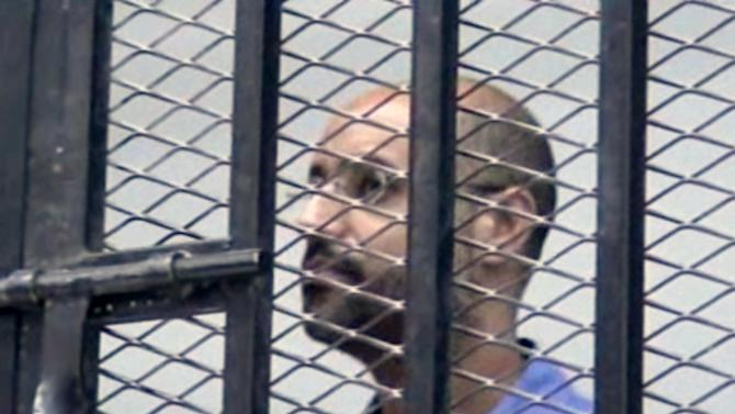 FILE - This image Thursday, Sept. 19, 2013 file photo made from AP video shows Seif al-Islam Gadhafi, son of Libya's former dictator Moammar Gadhafi, inside a cage in a courtroom in Zintan, Libya. A Libyan judge in the trial of former regime officials has decided that Moammar Gadhafi's son, held by a militia in the country's west, can attend the proceedings through a video link. Since the end of Libya's 2011 civil war, Seif al-Islam Gadhafi has been held by a militia in Zintan, which has refused to hand him over for a separate trial in the capital, Tripoli — a sign of the central government's weakness. Al-Islam faces charges along with 39 other Gadhafi regime figures — including notorious spymaster Abdullah al-Senoussi — for alleged crimes during Libya's conflict.(AP Photo via AP video, File)