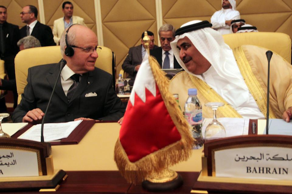 Bahrain's Foreign Minister Sheikh Khaled bin Ahmad al-Khalifa,Right, Speaks Algerian Minister of Foreign Affairs Mourad Medelci during the meeting of the Committee of Ministers of the Arab League to discuss the situation in Syria taking place in Doha, Tuesday 17, April 2012. (AP Photo/Osama Faisal)