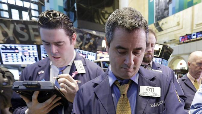 Trader Daniel Trimble, right, works on the floor of the New York Stock Exchange Wednesday, Feb. 6, 2013. Strong earnings reports from media giants Disney and Time Warner aren't impressing investors in early trading, and major U.S. market indexes are opening lower. (AP Photo/Richard Drew)