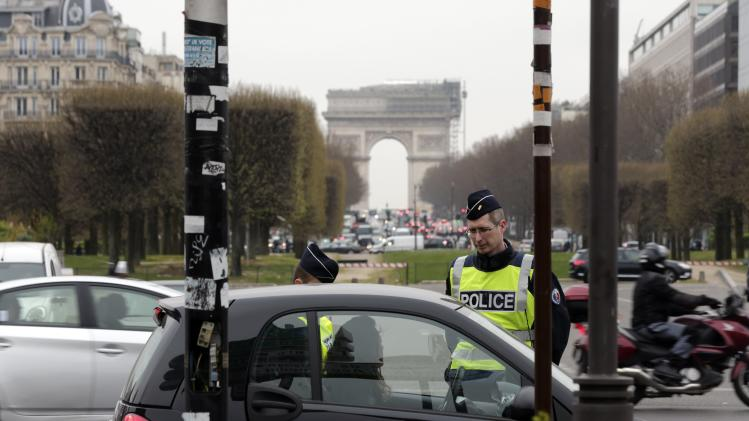 Police officers control cars with even-numbered licence plates which are not allowed to drive today, at Porte Maillot in Paris