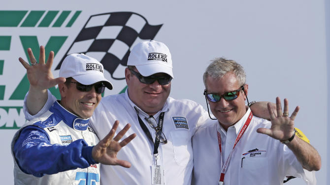 Driver Scott Pruett, Ganassi Racing team owner Chip Ganassi, and past champion Hurley Haywood, right, each hold up five fingers in Victory Lane, signifying five victories apiece, after the Grand-Am Series Rolex 24 hour auto race at Daytona International Speedway, Sunday, Jan. 27, 2013, in Daytona Beach, Fla. Pruett, Juan Pablo Montoya, Charlie Kimball and Memo Rojas won this year's race. (AP Photo/John Raoux)
